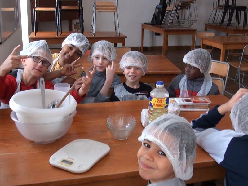 Groupe d'enfants en train de faire un gateau en colonie de vacances cuisine été