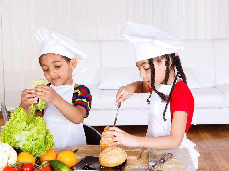 Enfants apprenant à faire la cuisine en binome en colonie de vacances
