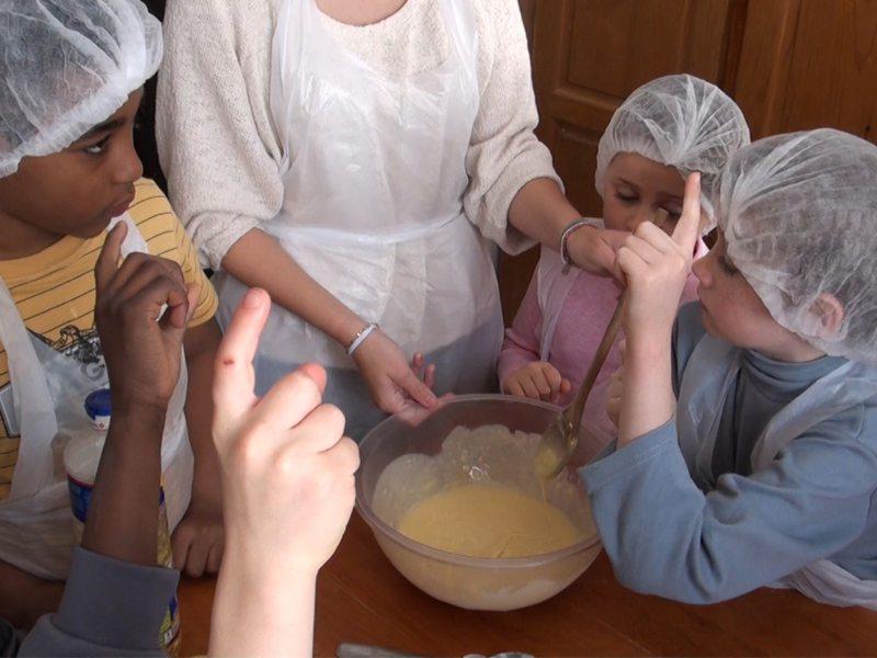 Groupe d'enfants apprenant à cuisiner avec leur animateur de colonie de vacances
