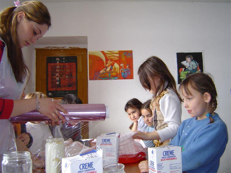 Animatrice de colonie de vacances et enfants apprenant à cuisiner en colonie de vacances été