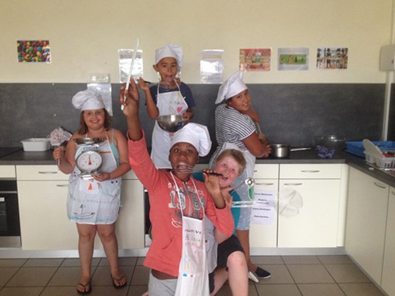 Groupe d'enfants vétus de toque et tablier posant en colonie de vacances cuisine