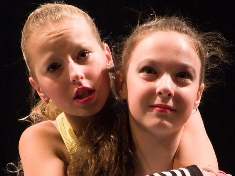 Portrait de deux jeunes filles sur scène faisant du théatre en colonie de vacances