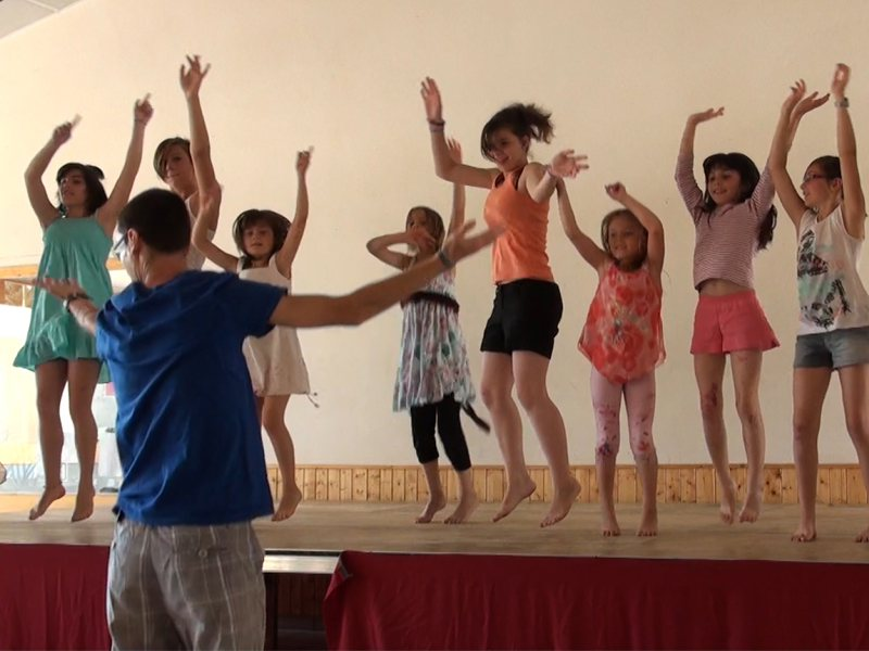 Groupe d'enfants sur scène apprenant une chorégraphie de danse sous les conseils de l'animateur de colo