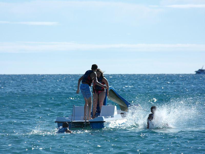 Enfants faisant du toboggan sur un pedalo à la mer en colonie de vacances