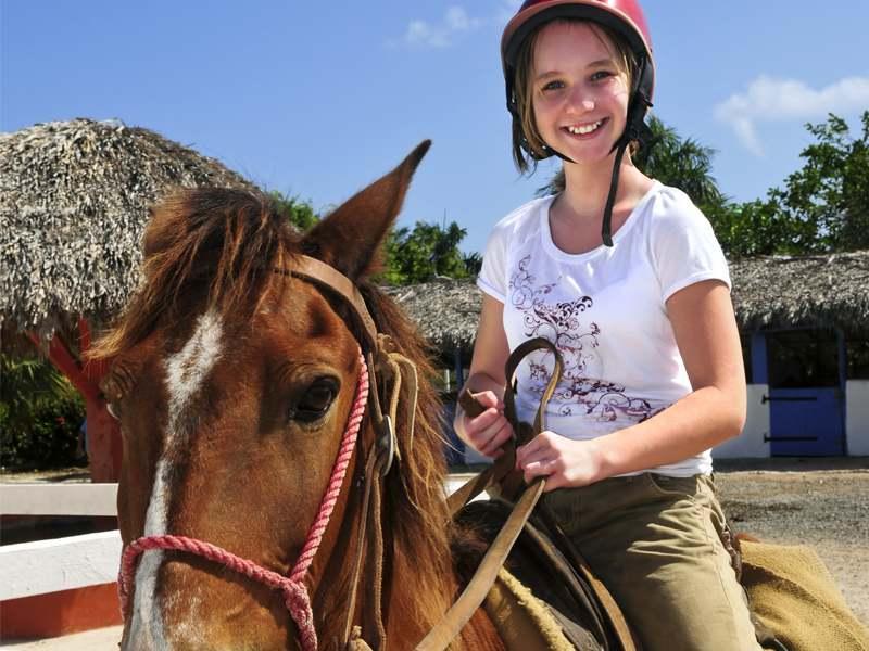 Portrait d'une jeune fille sur son cheval en colonie de vacances d'été