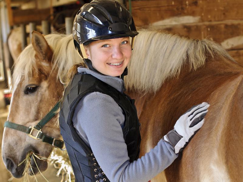 Jeune fille brossant son cheval en colonie de vacances équitation en camargues