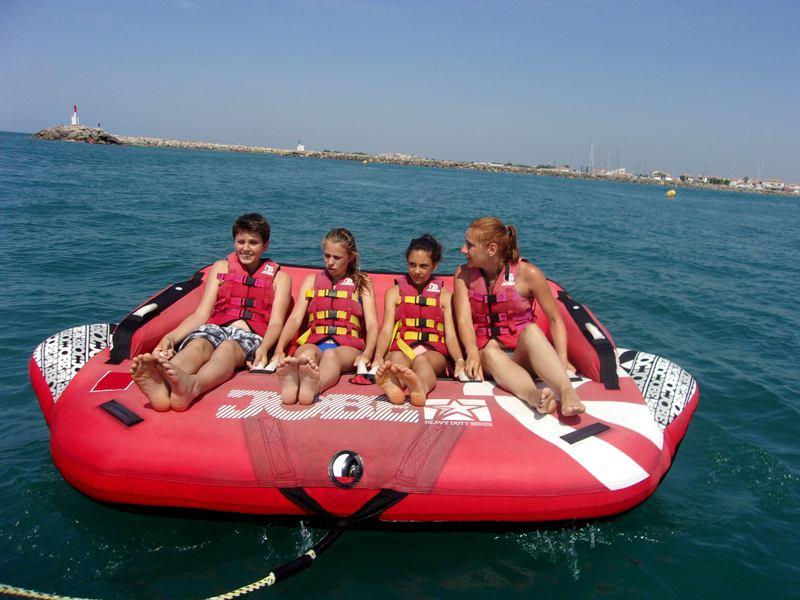 Enfants sur une bouée tractée en colonie de vacances d'été