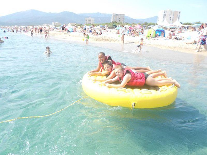 Enfants à la mer sur une bouée tractée en colonie de vacances