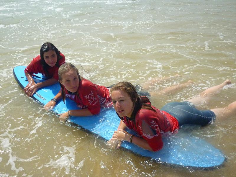 Trois jeunes filles à l'océan accoudées sur une planche de surf en colonie de vacances