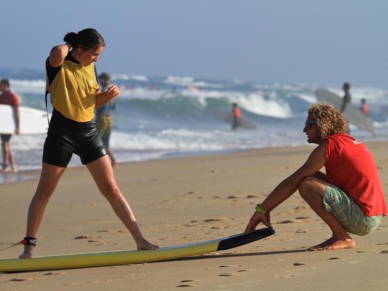 Adolescente apprenant la bonne posture pour faire du surf avec un moniteur de surf