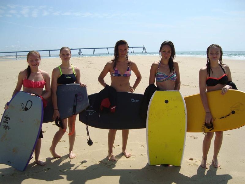 Groupe d'ados en colonie de vacances à la plage avec leur planche de surf