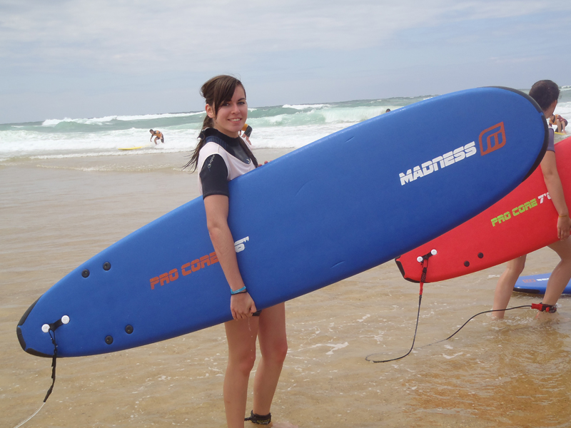Jeune fille à la plage avec sa planche de surf sous le bras, en colonie de vacances