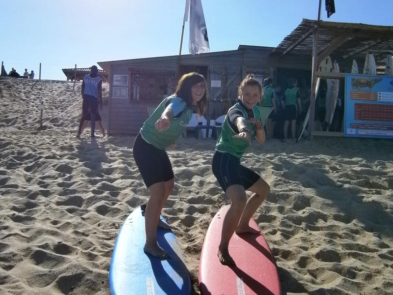 Adolescents apprenant à faire du surf en colonie de vacances d'été