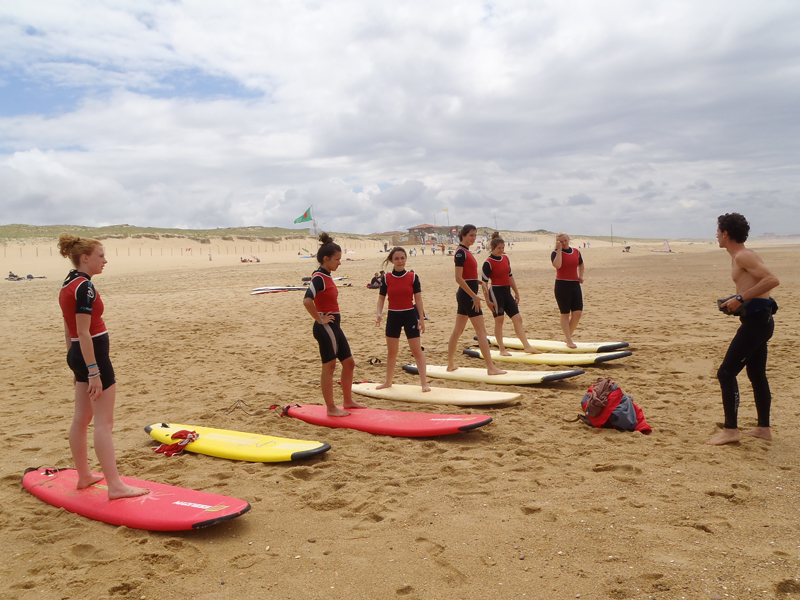 Groupe d'enfants sur la plage apprenant à tenir debout sur une planche de surf