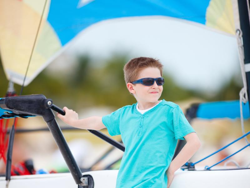 jeune garçon portant des lunettes de soleil à la plage en colonie de vacances surf