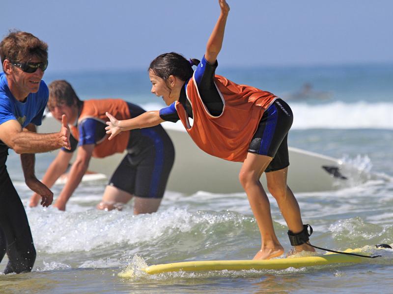 Jeune fille apprenant à trouver l'équilibre sur une planche de surf en colonie de vacances