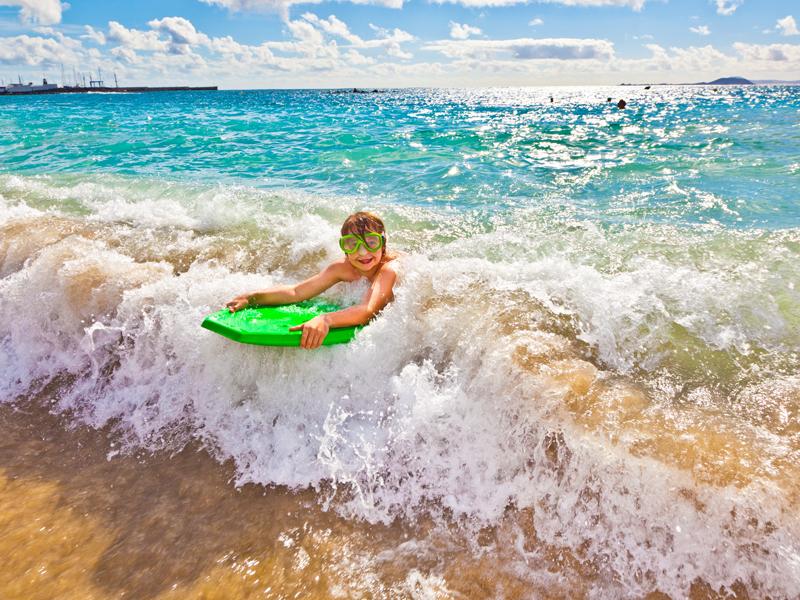 Jeune garçon apprenant à faire du surf en colonie de vacances atlantique en été