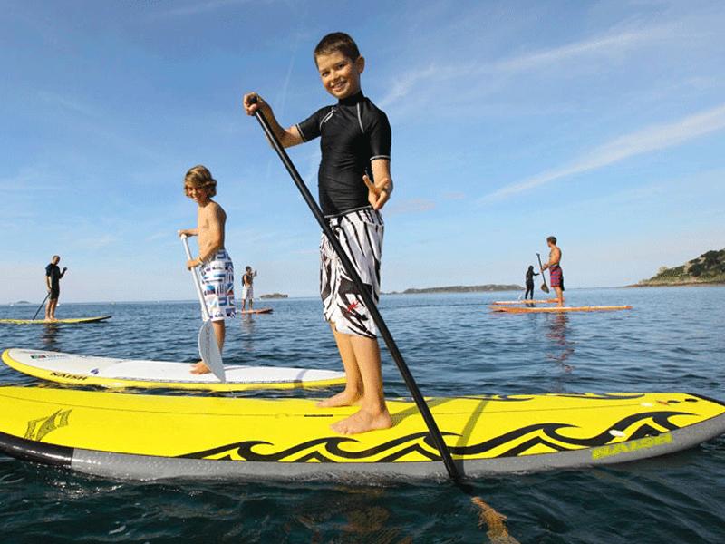 Enfants apprenant à faire du stand up paddle en colonie de vacances cet été