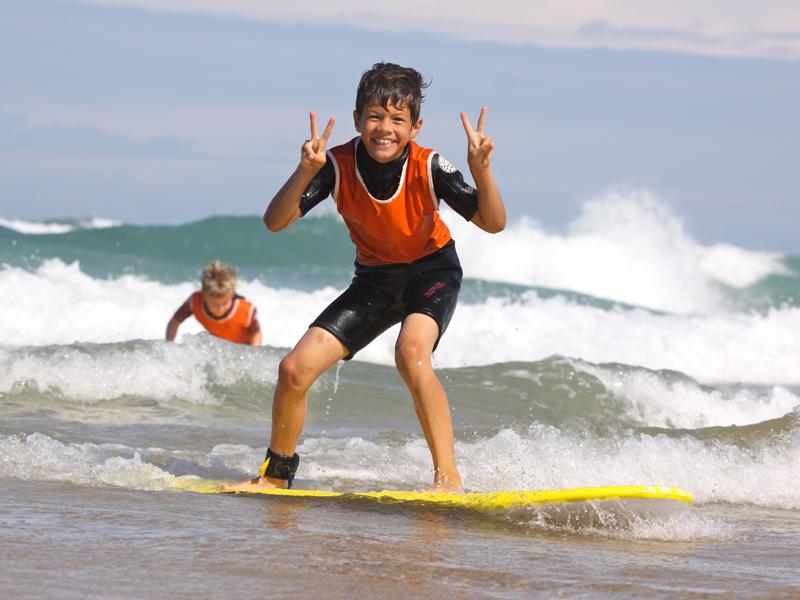Enfants heureux de faire du surf en colonie de vacances d'été