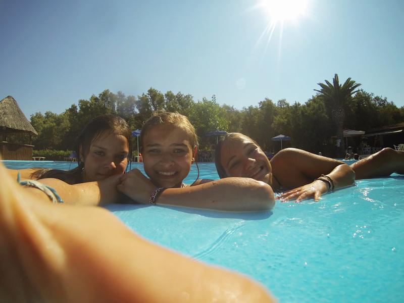 Groupe de preados en colonie de vacances se baignant à la piscine