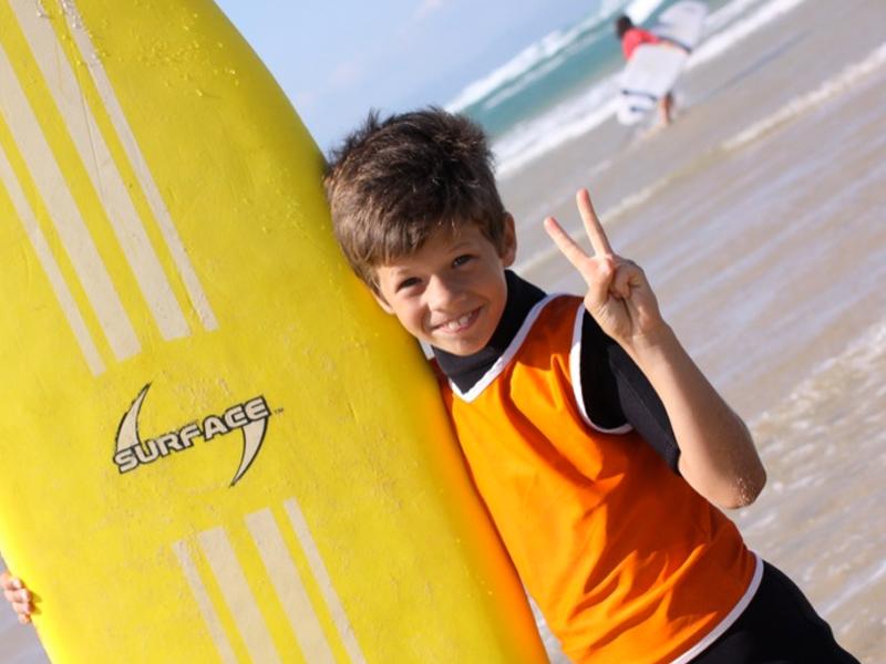 Enfant avec sa planche de surf en colonie de vacances d'été