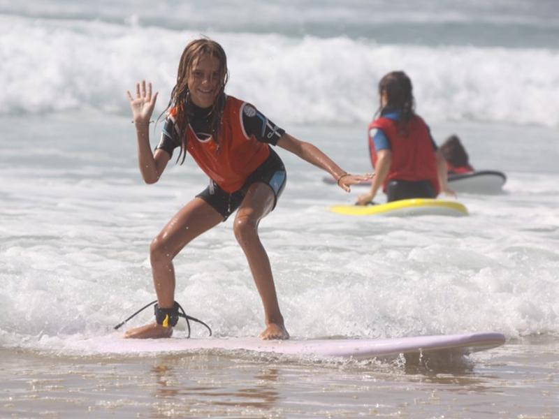 Jeune fille faisant du surf en colonie de vacances à l'océan atlantique