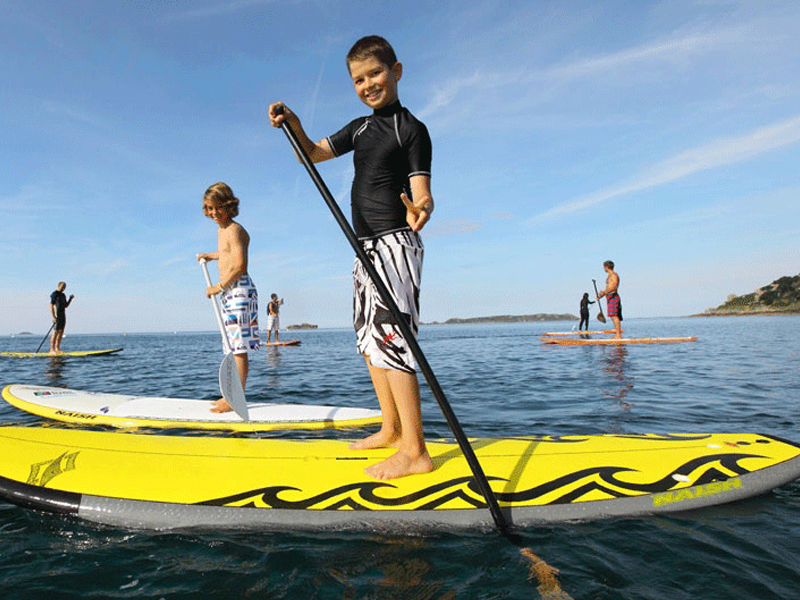 Enfants apprenant à faire du stand up paddle en colonie de vacances cet été