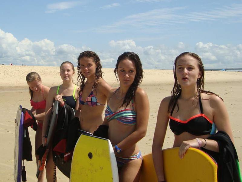 Jeunes filles sur la plage en colonie de vacances surf