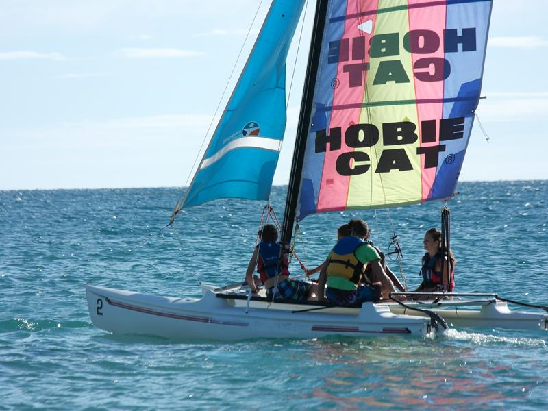 Enfants sur un optimist en colonie de vacances d'été