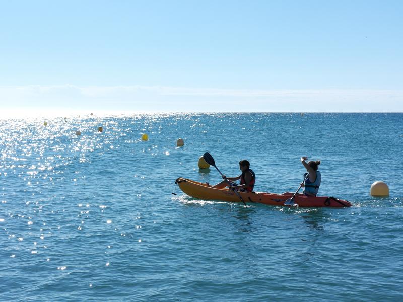 Enfants et adolescents faisant du canoe en colonie de vacances à l'océan
