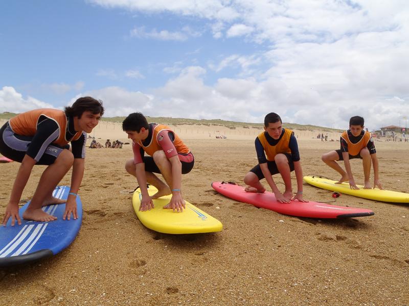 Adolescents apprenant à se positionner sur une planche de surf en colonie de vacances d'été