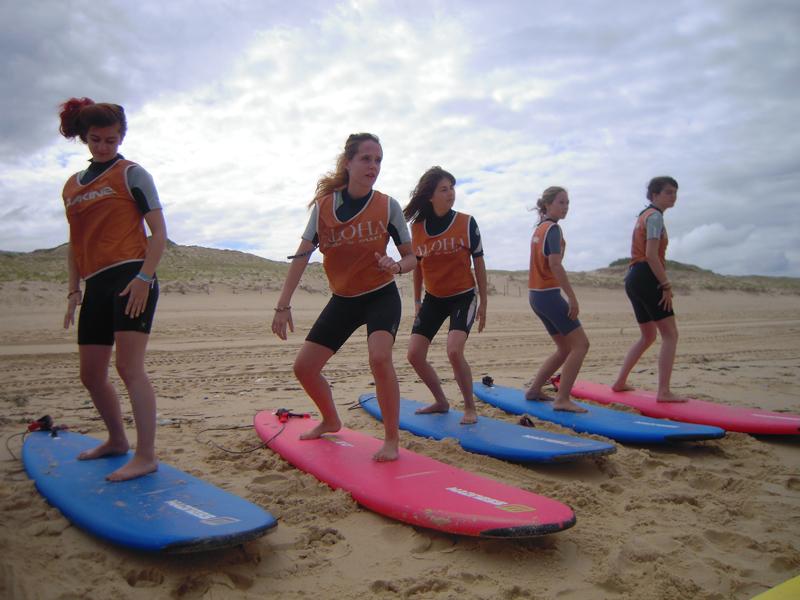 Adolescents apprenant la bonne posture sur un surf à la plage en colo