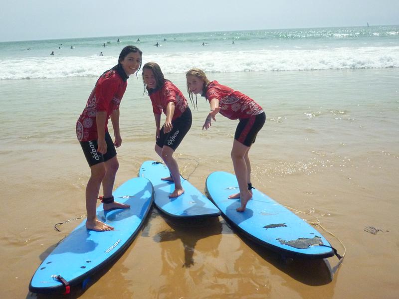 Trois jeunes apprenant à tenir debout sur un surf en colonie de vacances cet été