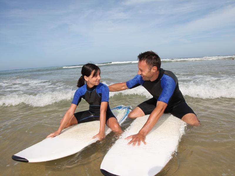 Moniteur de surf apprenant à une jeune fille à faire du surf en colonie de vacances