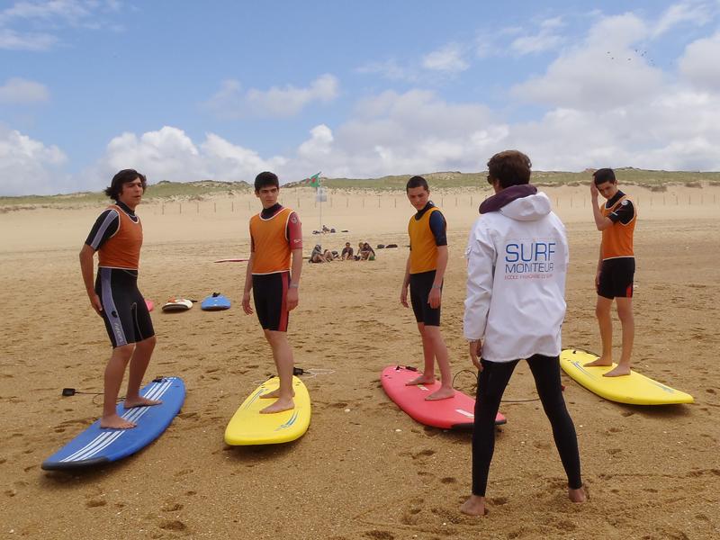 Moniteur de surf apprenant les bases à un groupe d'ados en colo de surf