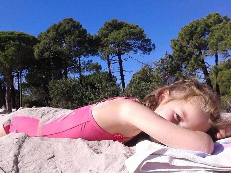 Fillette allongée sur la plage en colonie de vacances à la mer