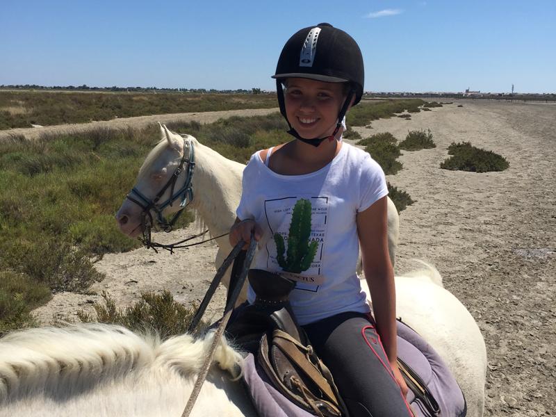 Fillette en balade à cheval en colonie de vacances en Camargue