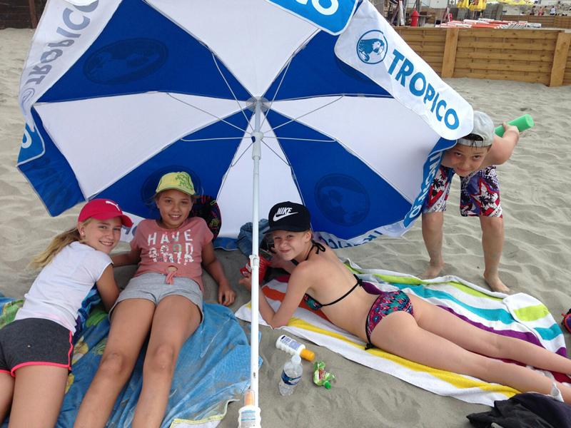 Enfants à la plage sous un parasol de colonie de vacances d'été