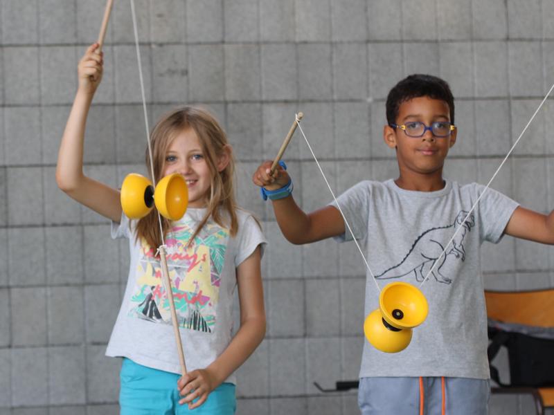 Un garçon et une fille apprenant à faire du diabolo en colonie de vacances cirque été