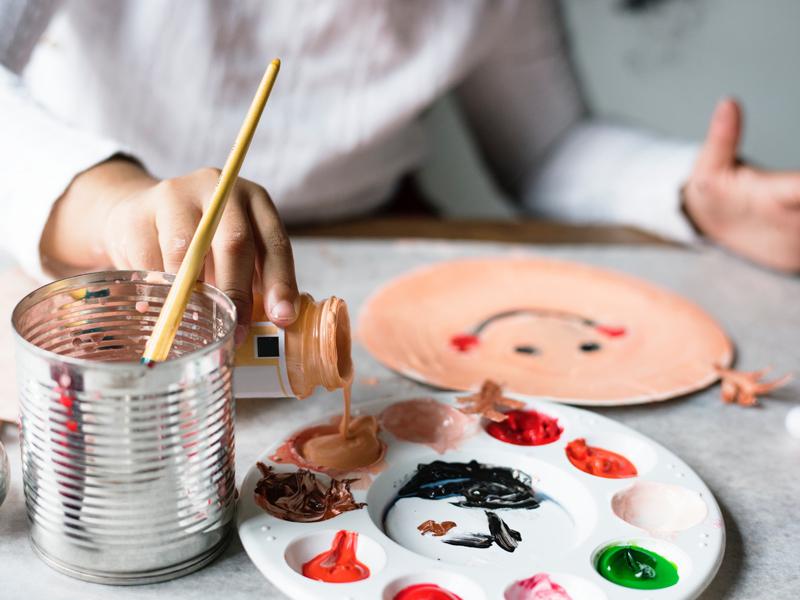 Enfant faisant des mélanges de peinture en colonie de vacances artistique été