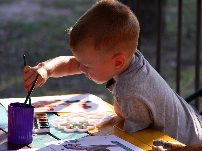 Enfant faisant des dessins en colo