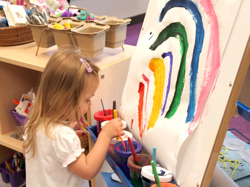 fillette faisant de la peinture en colo