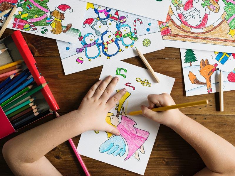 Enfant faisant des coloriages en colo cet été