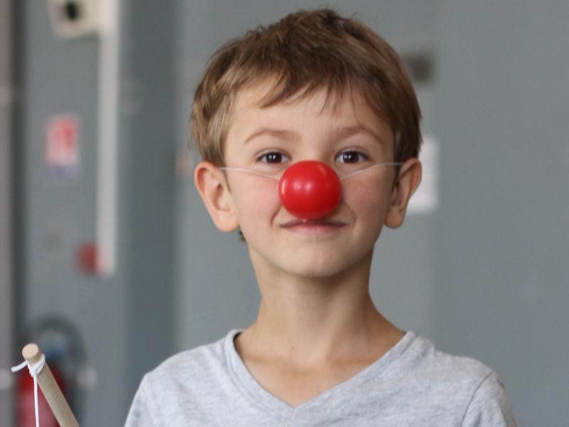 Jeune garçon portant un nez rouge de clown en colonie de vacances théatre