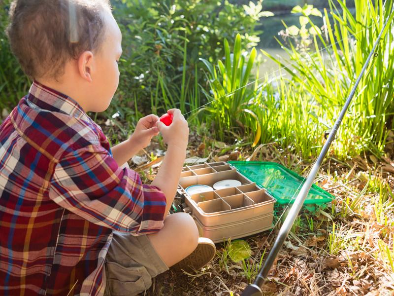 Petit garçon apprenant à se servir des flotteurs à la pêche en colonie de vacances