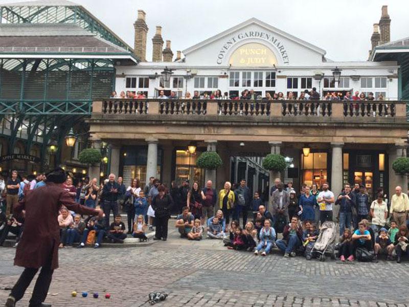 Un groupe d'adolescent regarde un spectacle de rue devant le Covent Garden Market à Londres en Angleterre