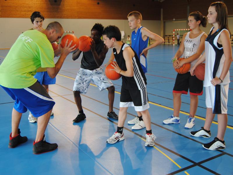 Enfants et ados jouant au basket en stage sportif