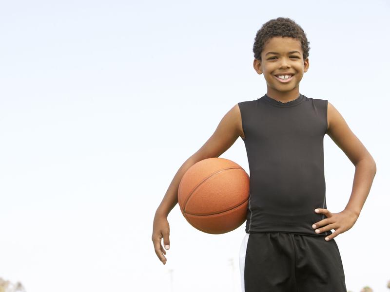 Portrait d'un jeune garcon faisant de basket en stage sportif
