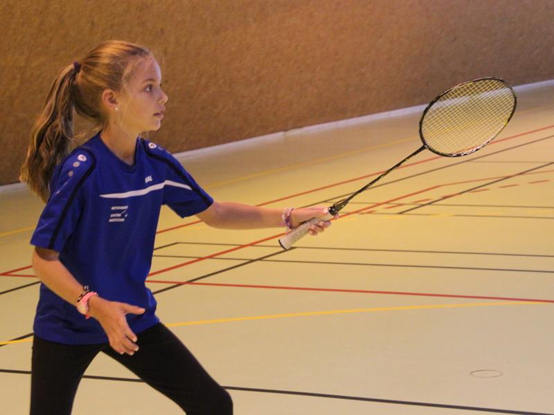 Jeune fille pratiquant le badminton à haut niveau en stage sportif de badminton