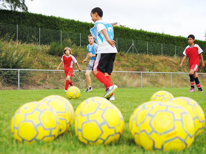 Enfants jouant au football cet été durant un stage sportif de football